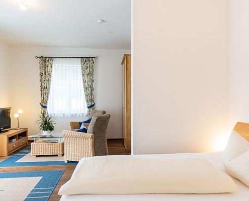 """Gästezimmer """"Amper"""" - Blick auf einen Schlafplatz und die Sitzgruppe"""